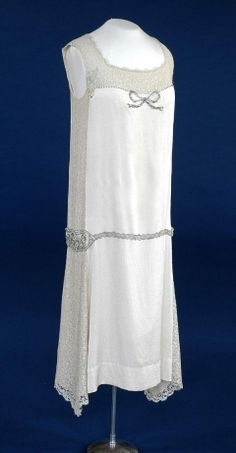 Wedding Dress, England, 1926 Wedding dress of cream silk/satin crepe and cream lace over pale peach silk, trimmed with diamante, pearls, silver beads and silver lace.