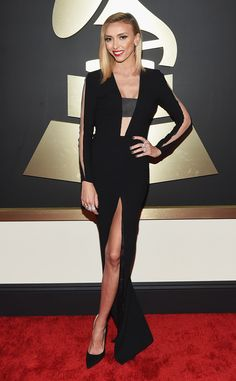 2015: Giuliana Rancic is wearing a black Steve Khalil gown with a slit, deep v neck with a bandeau, and cutouts on the sleeves. WOW! Giuliana stuns! I love her red carpet looks. This is one of my favorites. This gown is sexy and gorgeous.  I love the cutout long sleeves. Giuliana wore this for the Grammy pre-red carpet show on E!