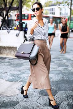 Gala Gonzalez wears a striped button-down shirt, high-waisted culottes, mary-jane heels, a Céline top handle bag, and black sunglasses