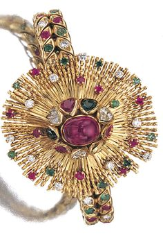RARE GEM-SET AND DIAMOND WRISTWATCH/BRACELET, STERLÉ, 1940S Decorated at the centre with a cabochon ruby supported by pear-shaped emeralds, rubies and diamonds, opening to reveal a circular golden dial applied with black Roman numerals, to the yellow gold fringes, cheveux d'ange, scattered with circular-cut rubies and emeralds, circular- and brilliant-cut diamonds, the straps set with similar stones, signed Sterlé and numbered, French assay marks,