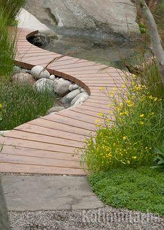 Siltamainen lautapolku sopii rakennettuun ympäristöön ja pelkistettyyn puutarhaan.