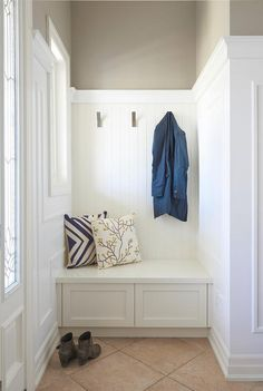 A white wainscoted built-in foyer bench is topped with blue and white pillows and is fixed in a nook against a white beadboard trim fitted with nickel coat hooks and contrasted with taupe upper walls painted in Benjamin Moore Museum Piece.