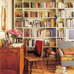 A wall of books with a comfy seat.