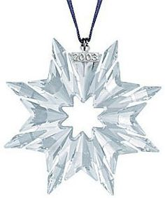 Swarovski 2003 Annual Crystal Christmas Ornament. Crystal star with a satin hanger band and a small silver tone tag with the year 2003. 3 inches tall.