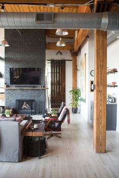 An industrial Chicago loft living room with exposed beams & ducts, and a gray painted fireplace wall.