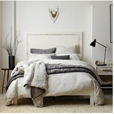 Neutral grey, white, and black color pallet bedroom. The antlers over the bed are perfect. - Apartmenttherapy.com
