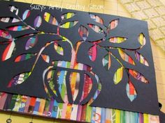cut out colourful strips from a magazine and glue to canvas. cut out a design from black paper and glue on top :):