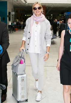 Karolina Kurkova wears a white button-down blouse, gray cardigan, matching skinny jeans, Converse sneakers, a pink scarf, and tortoiseshell sunglasses