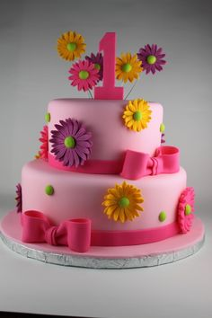 2 tier girly first birthday cake with bows and Gerber Daisys.
