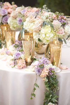 Lavender and blush pink roses, white hydrangeas. Floral garlands for the reception tables and sweetheart table. Gold mercury glass vases.
