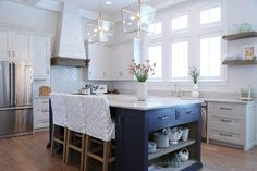 Glass and nickel lanterns hang over a blue kitchen island with open shelves topped with white quartzite kitchen countertops seating three white and gray trellis slipcovered counter stools.