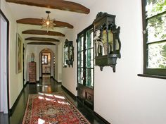 Ceiling beams, a Persian runner, and a slim, hand-painted chest make a narrow, sun-filled hallway interesting, and continue the ethnic vibe of the house.