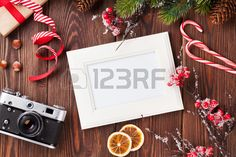 Blank photo frame with christmas gift box pine tree and camera on wooden table Top view Stock Photo