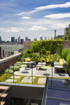 The new wooden rooftop terrace is surrounded by a green roof garden utilizing reclaimed bluestone pavers and native plant species that require little water while insulating the environment below.