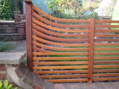 Contemporary cedar fencing curved upwards to accommodate height difference. We cut thin strips glued/screwed and clamped in place.