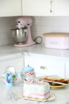 "MY KITCHEN MAKEOVER WITH  Formica Marble Countertops in the ""Amore"" edge. Makenzie Childs Butter Dish and Fioreware sugar and creamer. Pink Kitchenaid Mixer."