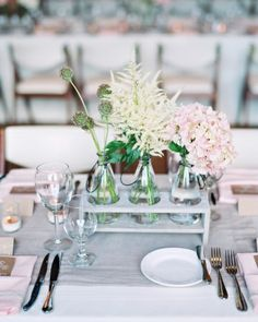 """Wooden Elements: """"Wooden stands held glass bottles of scabiosa pods, astilbe, and hydrangea at this outdoorsy wedding."""" - Martha Steward Wedding"""
