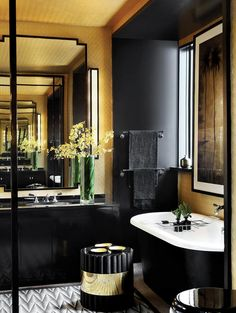 Dark and masculine bathroom in black, white, and gold. John Jacob Interiors