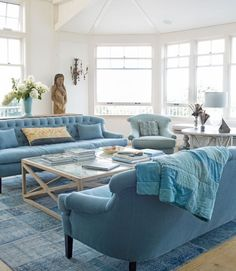 The living area's furnishings are awash in a sea of blues in this Martha's Vineyard home. A patchwork rug from Nomadic Trading Company anchors the room, furnished with linen sofas and a wingback chair by Cisco. The glass top on Groundwork's reclaimed-oak coffee table displays a collage of vintage art and family photos.