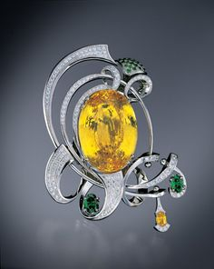 Sapphire Brooch. This platinum brooch has a 168-carat, yellow sapphire center stone, a 0.65-carat, yellow sapphire side stone, 3.46 carats of green diamonds and 2.92 carats of pave diamonds.
