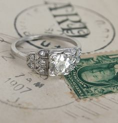 Art Deco Epaulet Diamond Engagement Ring $6,200.00    This magnificent late 1930s ring is set with a single, stunning .85-carat diamond, its rounded edges hugged by the four points of an elegant square setting—a popular design in the late 1930s and 1940s.