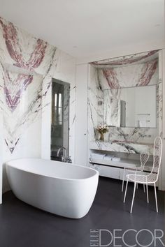 The tub in the master bath of this Paris apartment is by Agape, with fittings by Dornbracht, the chairs are by Junya Ishigami, the walls are clad in Brèche de Médicis marble, and the flooring is granite.