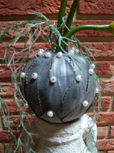 Een oud verkleurde vaas wat opgefrist met een mooi kleurdje.Daarop een piepschuimbol met in het midden een opening, bezet met blaadjes uit de fietsbanden geknipt. Op de vaas geplaatst met daarin 3 Calla's of andere buigzame bloemen.
