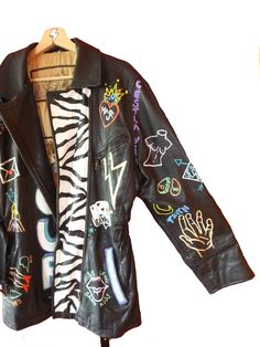 """Next  This vintage oversized leather jacket includes a mix of different drawings, patterns and words hand painted on them. The French word """"AMOUR"""" is written in large letters on the front. The lining on this jacket also makes this piece extra special!    www.mart-productions.com  Haindpainted One of a Kind Piece  Vintage genuine leather jacket"""