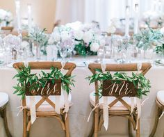Mr. and Mrs. chair signs decorated with green leaves, so chic!