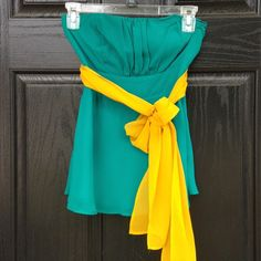 Teal tube top with matching yellow sash Gorgeous teal tube top with mustard yellow ribbon that ties. In absolute perfect condition-never been worn! Ruching and stretchy on the back. Looks great with skinny jeans and heels for a night out or with shorts for a hot summer day. Fully lined. 100% polyester. Thanks for looking. Fashion Spy Tops