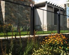 Simple and elegant, the lock crimp weave creates consistency in this beautiful bronze wire mesh fence, while also providing function by meeting code. Banker Wire L-81 is a medium duty mesh that can be woven in any wire alloy. The high percent open area and woven strength makes this a perfect mesh for all fence styles. Designing with a pre-crimped wire mesh for a landscape fence defines the perimeter . . . like a frame on a painting. Product(s) Used: L-81