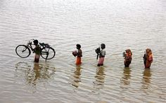 People from a nearby village carry their belongings through floodwaters at Ganjam district in the eastern Indian state of Odisha October 26,...