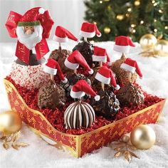 Santa and His Helpers Basket |   Let Santa & his nine little helpers sweeten your holiday celebration this year. This bountiful basket boasts a Peppermint Bark Jumbo apple clad in a festive Santa ornament. 9 Petite apples accompany Santa wearing mini, red stocking caps. Triple Chocolate, Milk Chocolate Walnut, Dark Chocolate Splendor, Dark Chocolate Delight, Dark Chocolate Cashew, Milk Chocolate Delight, Milk Chocolate Walnut Pecan, Milk Chocolate Toffee Walnut and Double Chocolate Peanut…
