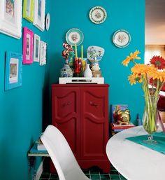 Assinada por Neza Cesar, a sala de almoço deste apartamento tem parede em tom de turquesa. Para enfeitá-la, além de quadrinhos em molduras, a designer de interiores usou pratos decorados