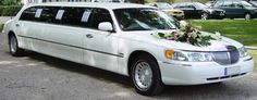 White wedding limo with flowers on the front.