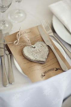 Ceramic heart ornaments made by the bride serve as place cards plus a super sweet, personalized favor.