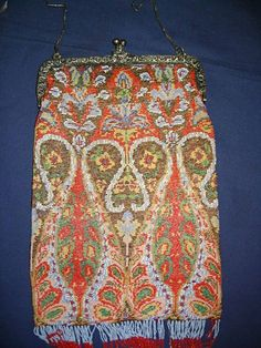 """A Victorian beaded bag with an ornate white metal clasp in the form of flowers and putti, stamped """"800"""", worked entirely in beaded knitting in a scrolling paisley style pattern (front and back), with twisted and interlocked two tone bead fringing along the bottom edge, chain link handle and fully lined with chocolate ultra suede trimmed with ribbon rose braid."""