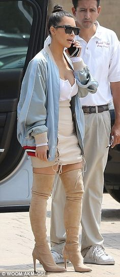 Slim again: Kim, who announced she's back to her pre-pregnancy weight, still opted to cover up her derriere with a lightweight jacket and was seen chatting away on her phone as she exited a silver Range Rover