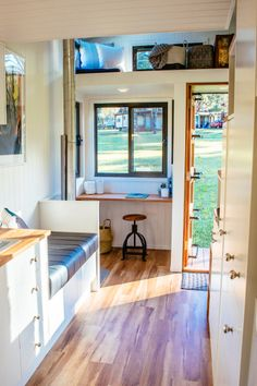 A storage loft is located over the entryway and writing nook area in this tiny house by Designer Eco Homes.