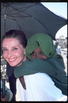 Ethiopia, 1988 - UNICEF Goodwill Ambassador Audrey Hepburn smiles as she carries a child on her back, under the shade of an umbrella, in the town of Mehal Meda in the northern part of the province of Shoa. Ms. Hepburn was visiting a food distribution centre in the town.  © UNICEF/NYHQ1988-0184/John Isaac  For more information, please visit: http://www.unicef.org