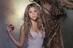 Shakira - with an apple in her hand, standing near a tree.