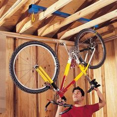 The Family Handyman DIY Tip of the Day: Movable Bike Rack. Cut four 3-1/2 in. blocks, stack two on top of each other, and screw them together. Now screw them on the end of a 4-ft. 2x4 and repeat the process for the other side. Then screw in the bicycle hooks. Lay the rack across the garage ceiling joists, and hang your bike from the hooks. When you need to get behind the bike, simply slide the rack out of the way.