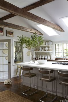 White Kitchen with wood beams & wood flooring. Walls are painted in Benjamin Moore's White Dove.