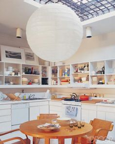 An Isamu Noguchi paper lantern in the kitchen of the SoHo loft of photographers Laura Resen and Cloud Devine; designer Thomas O'Brien collaborated on the interior; the 1930s library table and chairs are by Alvar Aalto. - ELLEDecor.com