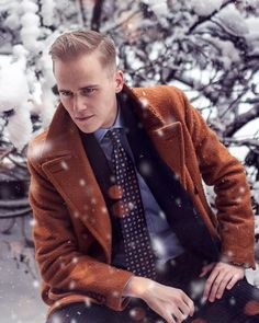 Dapper style with an overcoat and foulard tie.