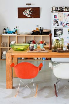 Colorful chair's and storage in this eclectic kitchen area of this Bohemian loft in Brooklyn. Pastel shades,flea market finds combined with a few modern touches and some carefully chosen classic pieces like the Wegner and Eames chairs make this loft a very cosy space despite everything being open plan.