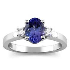 1.04 carat total weight 3-stone ring with .13 carat total weight round diamonds and a .91 carat oval tanzanite center stone prong set in 10k white gold.