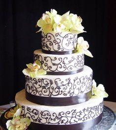 Four tier white round wedding cake with fresh flower petals and chocolate patterns.JPG