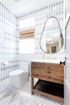 A Restoration Hardware Printmaker's Single Washstand sits on black and white cement floor tiles and is fitted with a white marble countertop holding a sink with a satin nickel faucet.