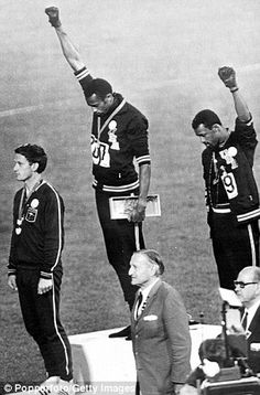 Power: Tommie Smith (center) and John Carlos (right) give the black power salute at the 1968 Olympic Games. Smith says that black Olympic legend Jesse Owens tried to persuade them not to give the salute